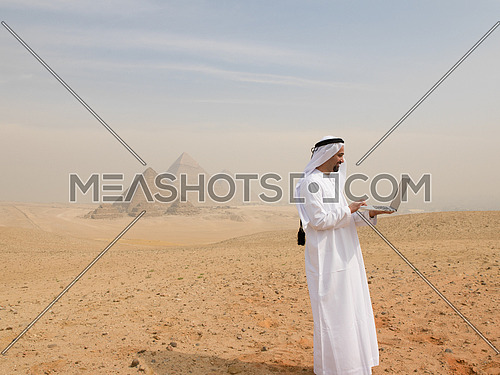 arabian business man using laptop computer in desert with great giza pyramids in background