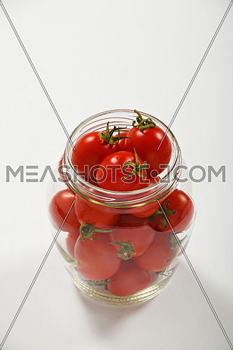 Glass jar full of red cherry tomatoes ready to pickle for conservation over white background, high angle view