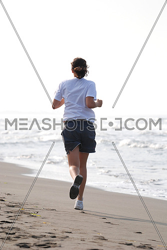 A young woman running by the beach
