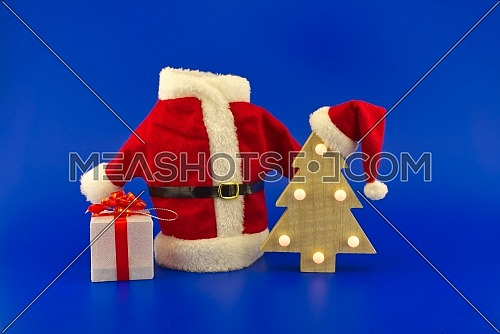 Red Santa Claus suit near stylized wooden Christmas tree with Santa hat and gift boxes on a festive blue background. New Year and Christmas gift season concept