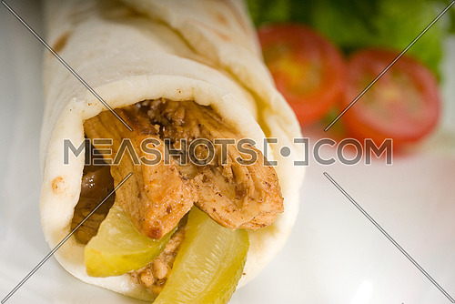 pita bread chicken roll with pickles cucumbers on a plate with pachino tomatoes and lettuce