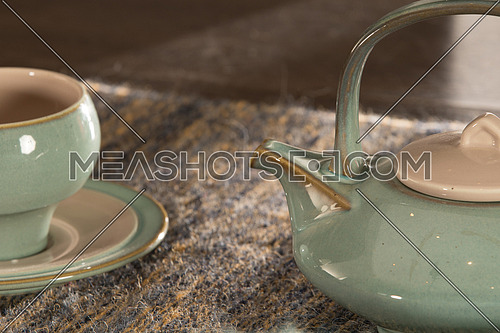 Tea pot on a rug and tea cup