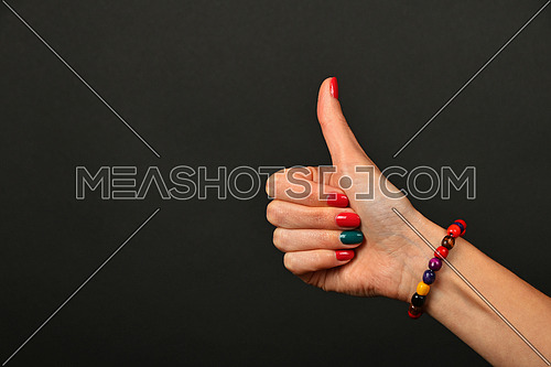 Woman hand with manicure nails and colorful wooden painted beads bracelet shows ok thumb up like gesture sign over black background
