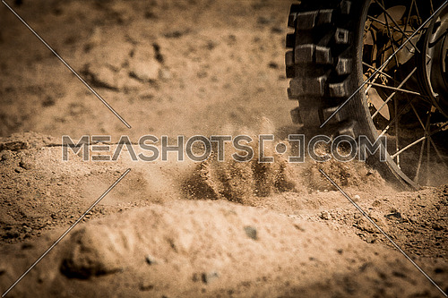 close up of a Speeding Bike on a sandy trail