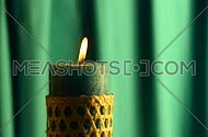 Teal candle with straw twigged holder trembling flame close up out of the dark green folded fabric cloth background, off-center, blown out