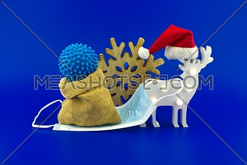 Christmas deer scene with coronavirus gift in sack bag on the sleigh made of medical face mask. Miniature isolated on blue background