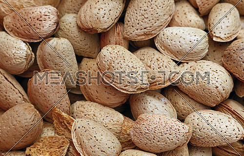 Whole raw brown almond nuts with shell on retail market, close up, background, high angle, elevated top view