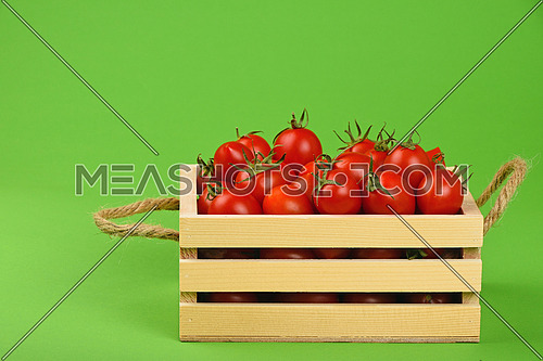 Red ripe fresh cherry tomatoes in small wooden box with twine jute handles on green paper background, side view
