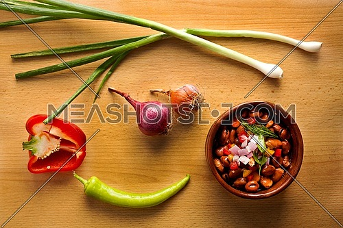 this is a shot for Egyptian beans (foul) plate on a wooden table with onions and pepper... egyptian breakfast
