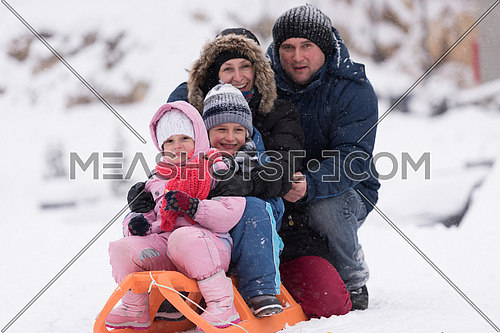 happy young family portrait on winter vacation while sitting sledge at  landscape with fresh falling snow