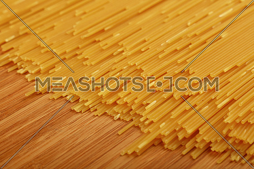 Close up background pattern of dry uncooked spaghetti pasta on wooden board, high angle view