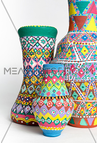 Three pieces of colorful decorated painted oriental pottery vases on white background