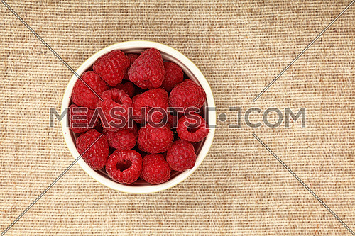 Close up one ceramic bowl of fresh red ripe raspberry over linen canvas tablecloth, elevated top view, directly above