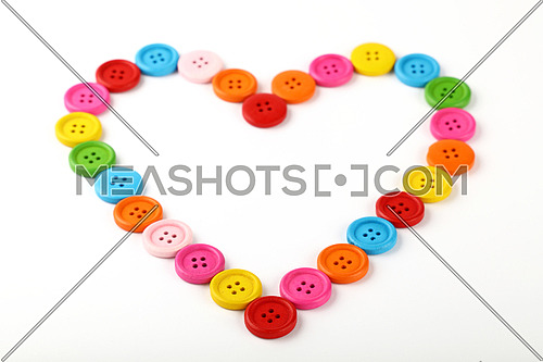 Heart shaped frame of colorful multicolor round painted wooden handmade sewing buttons isolated on white, close up, high angle view