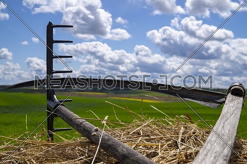 Rake and scythe on dried straw against a sunny blue sky with white clouds