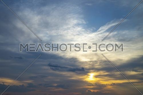 Glowing sun peeking through the clouds at sunset in a twilight blue sky in a nature or weather background with copy space