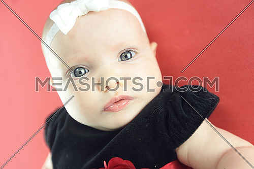 A cute baby wearing a dotted dress isolated on red