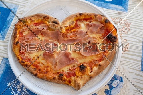 Heart shaped pizza with tomatoes and ham for Valentines Day on white plastic plate on the table,Food concept of romantic love