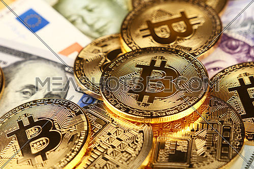 Close up heap of golden bitcoin physical coins on top of Euro, dollar, pound and yuan paper currency banknotes background, high angle view, selective focus