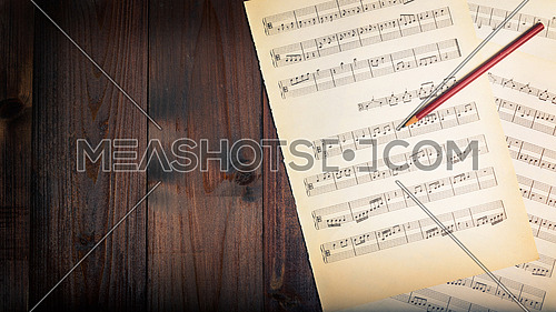 In the picture aged pages of sheet music, pencil  and wooden background,used split tonig for old/vintage style, above view.