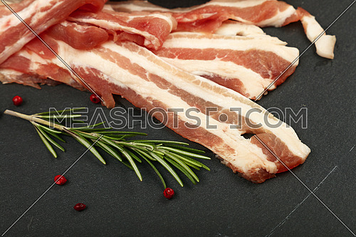 Raw pork bacon slices, rashers, spices, rose peppercorns and fresh rosemary leaves on black slate board, close up, high angle view