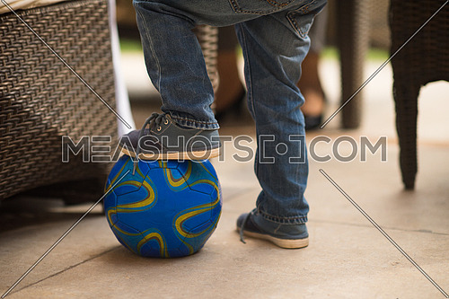 child putting his foot on a ball