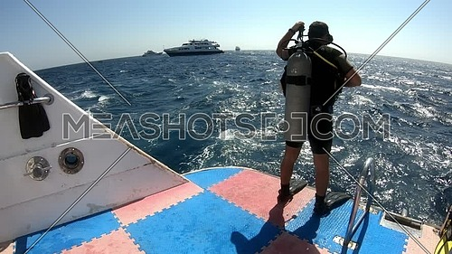 Long shot for diver getting ready to dive into Red Sea from a yacht at day