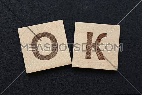 Close up word OK on wooden scrabble letter signs over black board background