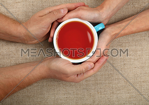 Man and woman hands holding and hugging together big full cup of black tea over canvas tablecloth, close up, elevated top view