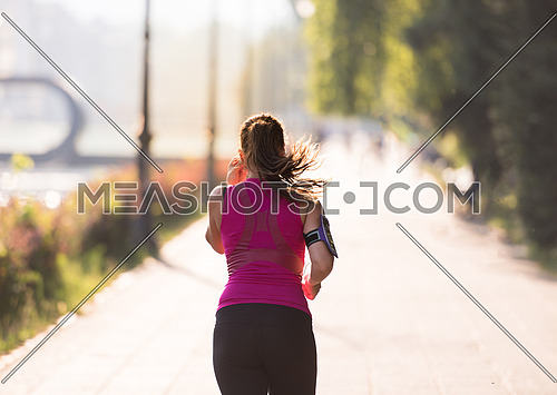 young sporty woman jogging at sunny morning in the city