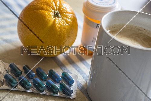 Medication during breakfast, capsules next to a orange, conceptual image