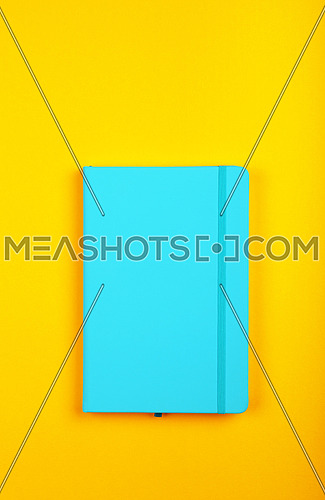 One closed blue faux leather cover notebook on vivid yellow paper background, flat lay, directly above