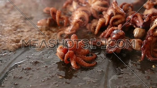 Close up of cooking seafood baby octopus, sizzling in oil and sauce on big frying pan, high angle view