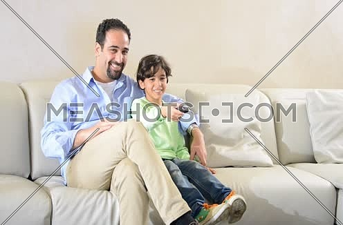 Mid shot for a father and son watching TV holding remot control
