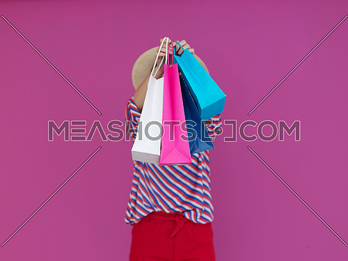 Girl holding shopping bags in front of her face. Black Friday concept of big sales