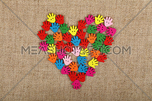 Heart of human hand palm shaped handmade colorful multicolor wooden painted sewing buttons on linen canvas, elevated top view