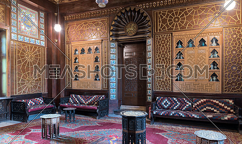 Manial Palace of Prince Mohammed Ali. Guests Hall with wooden ornate ceiling, wooden ornate door, lanterns, colorful ornate couches, tea tables and ornate carpet