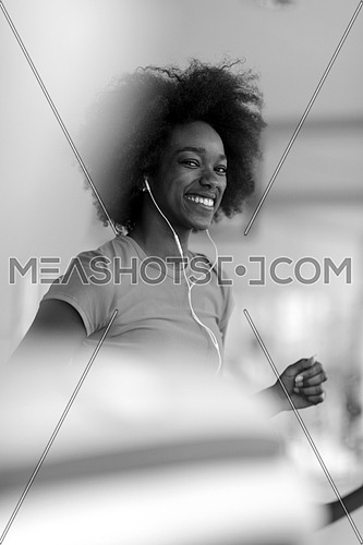 afro american woman running on a treadmill at the gym while listening music on earphones