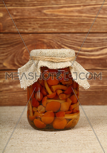 Close up of one glass jar of pickled small brown honey fungus Armillaria mushrooms with canvas top decoration and twine on canvas tablecloth over brown wooden background, low angle side view