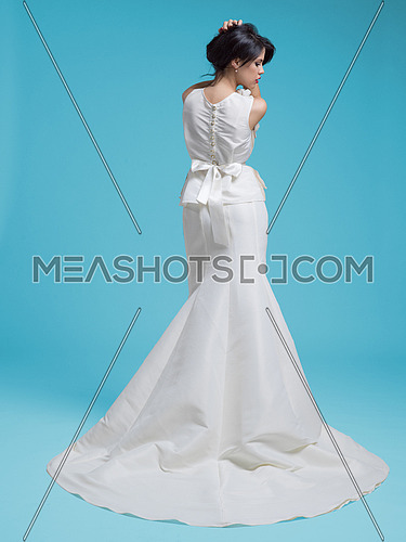 Portrait of beautiful young women in wedding dress isolated on a cyan background
