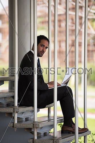 Young handsome middle eastern business executive sitting on steps in a corporate offices building using laptop