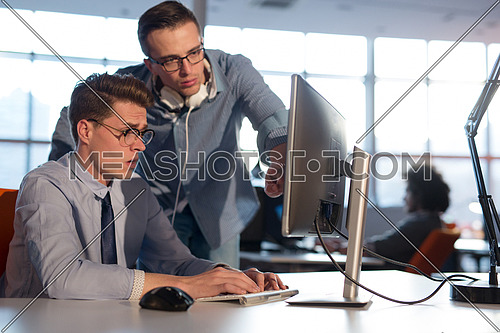 two business people using computer preparing for next meeting and discussing ideas with colleagues in the background
