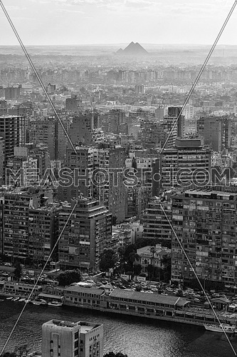 black and white aerial view of modern Cairo city downtown with Nile and pyramids in the distance at beautiful sunny day with blue sky and clouds capital of Egypt