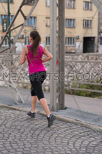 young sporty woman jogging across the bridge at sunny morning in the city