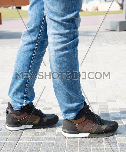 female legs wearing jeans and wearing sneakers