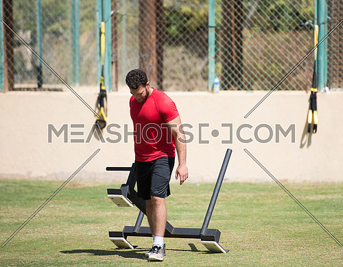 young middle eastern athletic man hard workout battle ropes outside on a sunny day