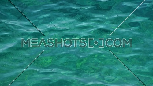Close up background of emerald green and turquoise sea ripples running on water surface, high angle view