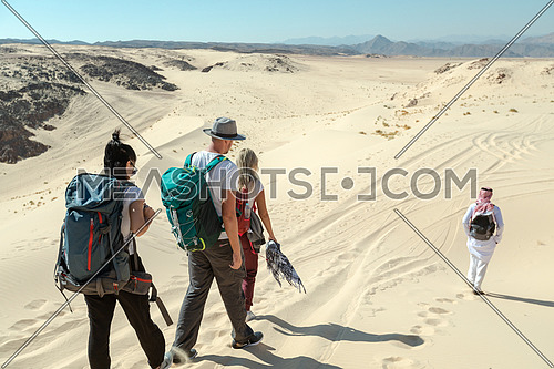 Long shot for group of tourists walking on sands with bedouin guide while exploring Sinai Trail from Ain Hodouda by day.