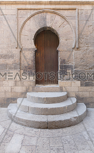 Wooden aged vaulted door, three steps and stone wall, Medieval Cairo, Egypt