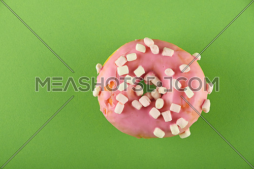 Round ring donut in pink glaze with small marshmallows topping decoration on green paper surface